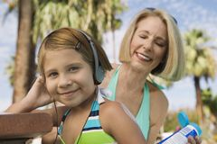Grandmother applying sunscreen to girl (7-9) listening to headphones portrait. Stock Photo