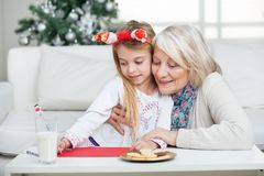 Grandmother Assisting Girl In Writing Letter To Stock Images