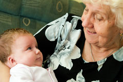 Grandmother with baby. Grandmother holding baby granddaughter, they are looking at each other Royalty Free Stock Photos