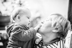 Grandmother with baby boy. Happy love moment together, monochrome Stock Image