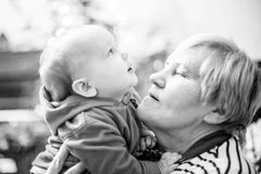 Grandmother and grandson infant. Grandmother with baby boy, happy love moment together, monochrome Stock Image