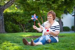 Grandmother and baby boy playing with a pinwheel on a  green lawn Stock Photo