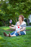 Grandmother and baby boy playing with a pinwheel outside Royalty Free Stock Photography