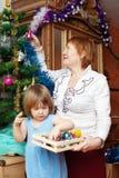 Grandmother and baby gilr decorating Christmas tree Royalty Free Stock Photography