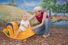 Grandmother and baby playing and having fun on toy. Grandmother playing with happy baby on plastic toy Royalty Free Stock Images