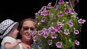 Flowers for decoration. Ampelous flowers. Grandmother with baby watering flowers.