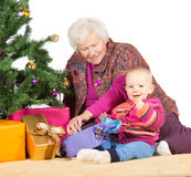 Grandmother babysitting young baby. Sitting together on the floor alongside a decorated Christmas tree and giftwrapped presents stock photography