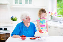 Grandmother baking cake with granddaughter Stock Photo