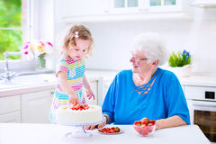 Grandmother baking cake with granddaughter Stock Images