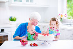 Grandmother baking cake with kids. Happy senior lady, loving grandmother, baking a homemade strawberry cake with two children, cute laughing baby boy and Stock Photography