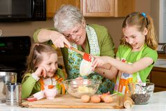 Grandmother baking cookies with children. A sweet Grandmother baking cookies at home with two children Royalty Free Stock Photography