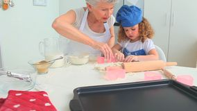 Grandmother baking cookies with her grand daughter stock footage