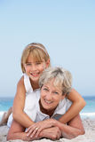 Grandmother On Beach With Granddaughter. Grandmother Relaxing On Sandy Beach With Granddaughter Smiling At Camera Royalty Free Stock Images