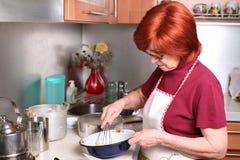 A grandmother beats eggs Royalty Free Stock Photos