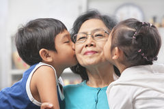 Grandmother being kissed by grandchilds. Grandmother being kissed by grandchildren at home Royalty Free Stock Photo