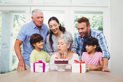 Grandmother blowing birthday candles with family. At home stock images