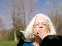 Grandmother Blows A Kiss. Head and shoulders shot of a senior citizen woman blowing a kiss goodbye toward the viewer.  Outdoor setting.  Shallow depth of field Stock Images
