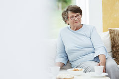 Grandmother in blue outfit. Is sitting on sofa in common room with yellow wall Royalty Free Stock Photos