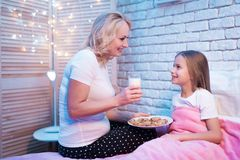 Grandmother brings granddaughter cookies and milk at night at home. royalty free stock image