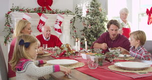 Grandmother brings out Christmas turkey to family seated around table for lunch. Parents help to serve vegetables to children stock footage