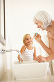 Grandmother Brushing Teeth With Granddaughter. Grandmother Brushing Teeth In Bathroom With Granddaughter Watching royalty free stock images