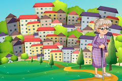 A grandmother with a cane walking at the hilltop Royalty Free Stock Image