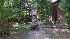 Grandmother carries blonde toddler in pram stock video footage
