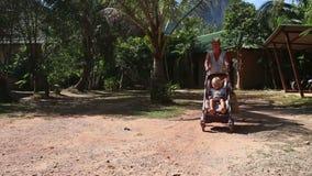 Grandmother carries blonde toddler in pram stock video