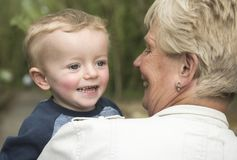 Grandmother carrying her happy two year old grandson royalty free stock photography