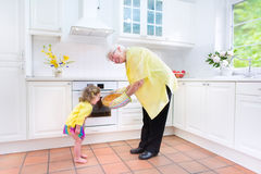 Grandmother and charming girl baking pie in white kitche Royalty Free Stock Photo