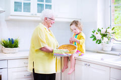 Grandmother and charming girl cooking pie in white kitche. Happy beautiful great grandmother and her adorable granddaughter, curly toddler girl in colorful dress Stock Photo