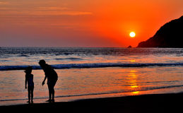 Grandmother and child at the beach. Grandmother and child looking for shells during sunset Stock Photo