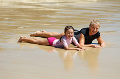 Grandmother and child at the beach. Grandmother and grand-daughter at a quiet  beach lying on the sand and having fun family time holiday together Royalty Free Stock Photography
