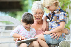 Grandmother with children playing on tablet Stock Images