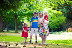 Grandmother and children walking in a park. Grandmother and grandchildren enjoying picnic in a park. Grandma playing with children in a sunny autumn forest Royalty Free Stock Photo