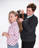 Grandmother combing hair her granddaughter Stock Photography
