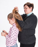 Grandmother combing hair her granddaughter Stock Images