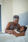 Grandmother comforting sick granddaughter in bed room. At home Stock Images