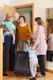 Grandmother coming to family  home. Cheerful grandmother with luggage coming to family with two children home Stock Photos