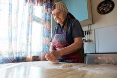 Grandmother cooking bakery products, fresh bread, tasty pie. Senior woman kneading the dough in her home kitchen, grandmother cooking bakery products, fresh royalty free stock image