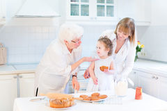 Grandmother cooking with daughter and granddaughter. Grandmother having fun with her daughter and granddaughter - a cute curly toddler girl - in a beautiful Royalty Free Stock Image