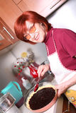 A grandmother is cooking a jam tart. A smiling grandmother is cooking a jam tart Royalty Free Stock Photography