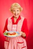 Grandmother Cooks Italian Spaghetti. Sweet retro grandmother holding a plate of fresh, hot Italian Spaghetti with marinara sauce.  Red background Royalty Free Stock Photo