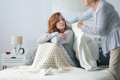 Grandmother covering woman with flu. Grandmother covering young women with flu sitting on a bed with a sweater Stock Photos