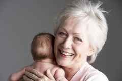 Grandmother Cuddling Granddaughter Stock Photo