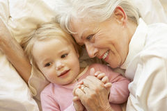 Grandmother Cuddling Granddaughter In Bed stock photos