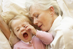 Grandmother Cuddling Granddaughter In Bed stock image