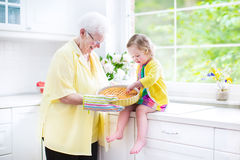 Grandmother and cute girl baking pie in white kitchen. Happy beautiful great grandmother and her adorable granddaughter, curly toddler girl in colorful dress Royalty Free Stock Photography