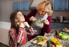 Grandmother and cute granddaughter cooking salad. Grandmother and cute granddaughter cooking healthy food at home at kitchen Royalty Free Stock Photography
