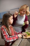 Grandmother and cute granddaughter cooking salad. E view image of girl cutting lettuce for salad. grandmother eating lettuce nearby Royalty Free Stock Photo